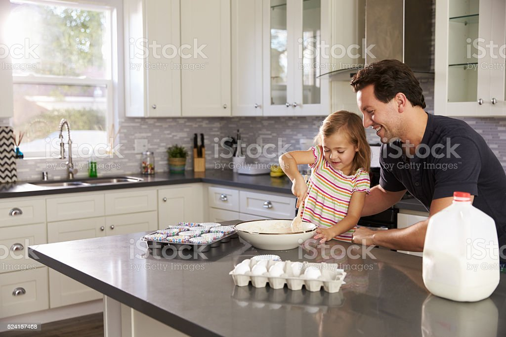 Caucasian girl and dad baking together in the kitchen stock photo