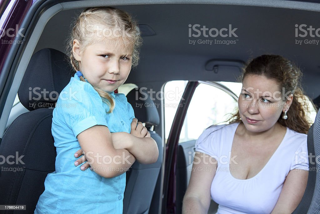 Caucasian girl does not want fastening in child safety seat royalty-free stock photo
