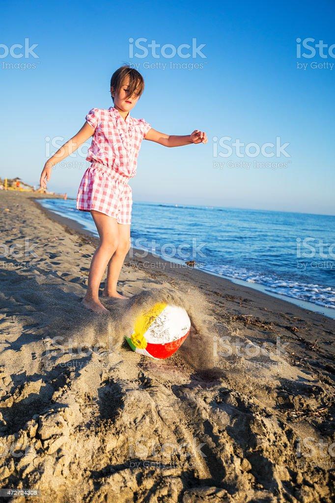 Caucasian girl kickinc beach ball stock photo
