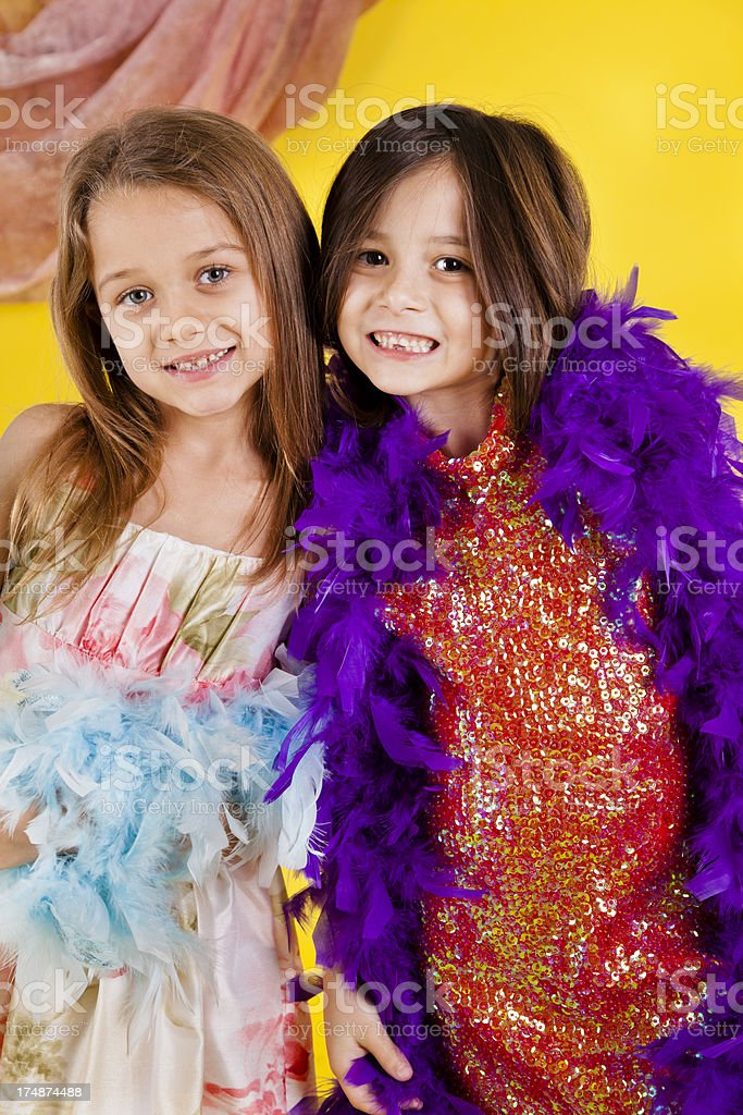 Caucasian girls 7-8, playing dress up with feather boas royalty-free stock photo