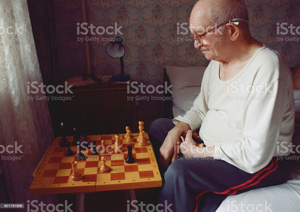 caucasian grand father in eyeglasses thinking chess strategy stock photo
