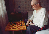 caucasian grand father in eyeglasses thinking chess strategy