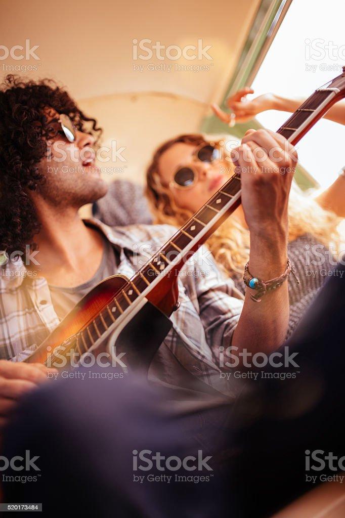 Caucasian Hipster Woman Smiles at Mixed Race Man Playing Guitar stock photo
