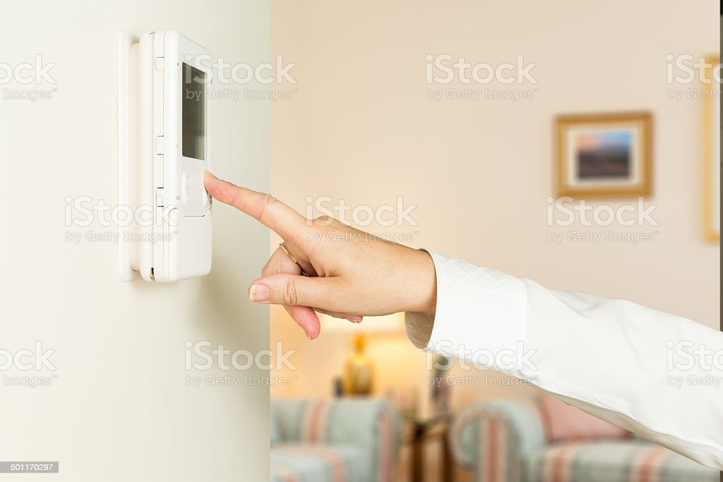 Caucasian lady pressing modern thermostat stock photo