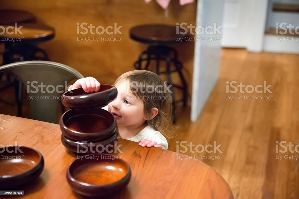 Caucasian little girl stacking bowls on kitchen table stock photo