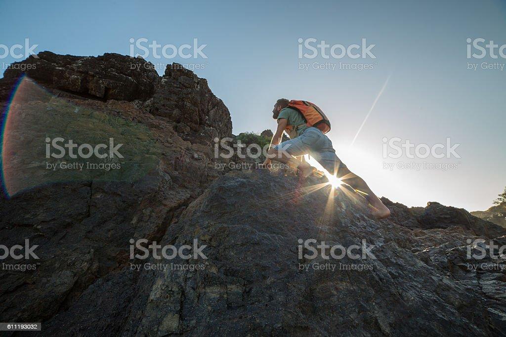 Caucasian male climbs steep rock, towards sunlight stock photo