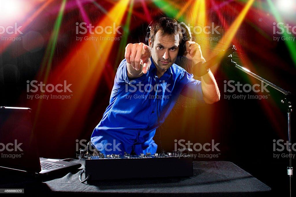 Caucasian Male DJ Wearing a Blue Shirt Pointing Forward stock photo