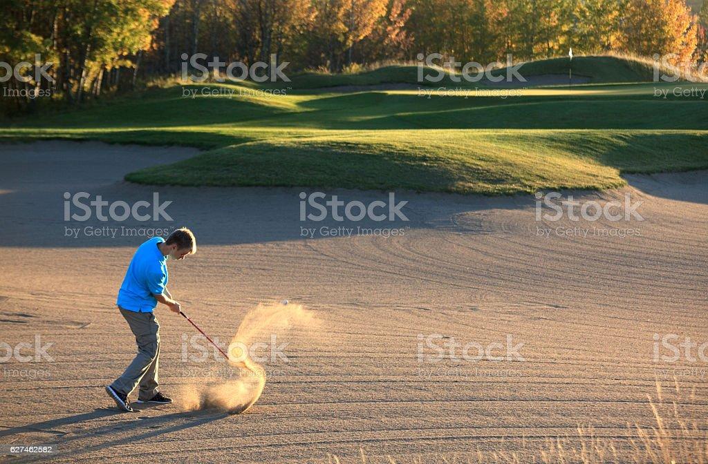 Caucasian Male Junior Golfer Hitting Bunker Shot stock photo