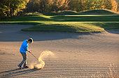 Caucasian Male Junior Golfer Hitting Bunker Shot
