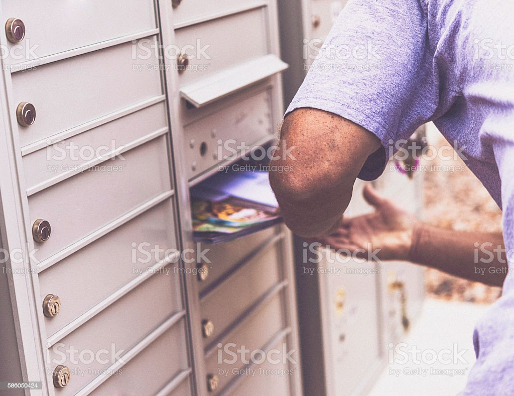 Caucasian male retrieving mail from mailbox stock photo