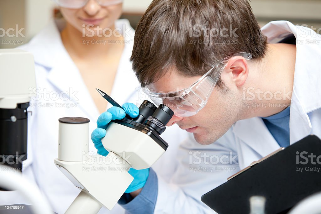 Caucasian male scientist holding pen and clipboard looking throu royalty-free stock photo