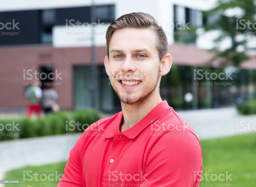 Caucasian male student with stubble looking at camera stock photo