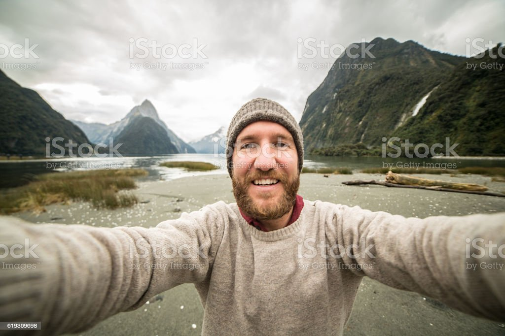 Caucasian male traveling takes selfie portrait with mountain landscape stock photo
