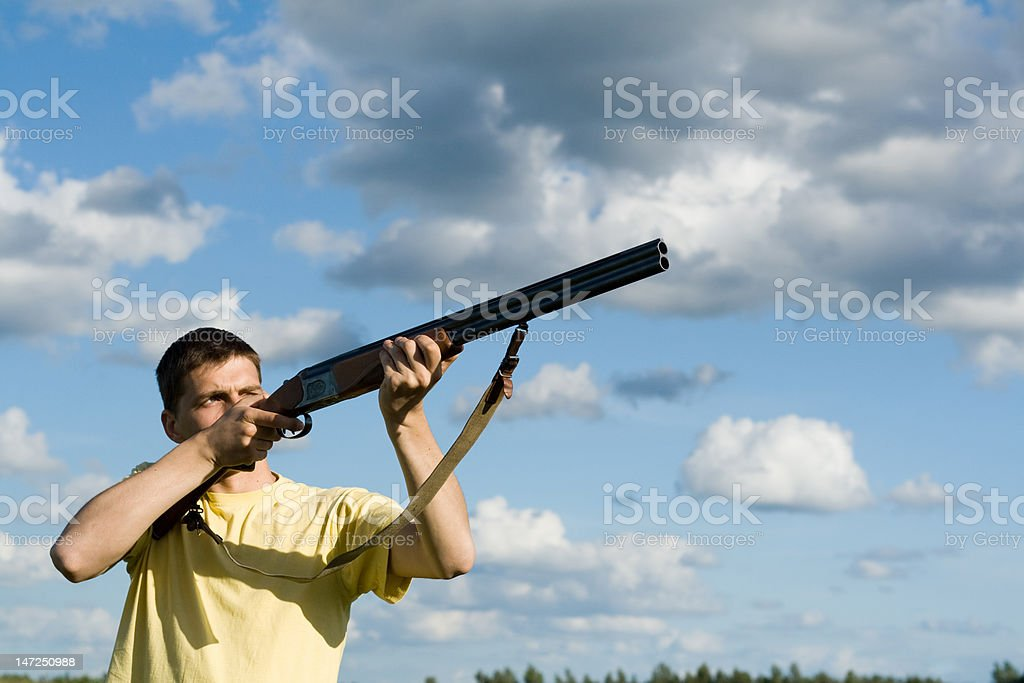 Caucasian man aiming. Cloudy sky background. royalty-free stock photo