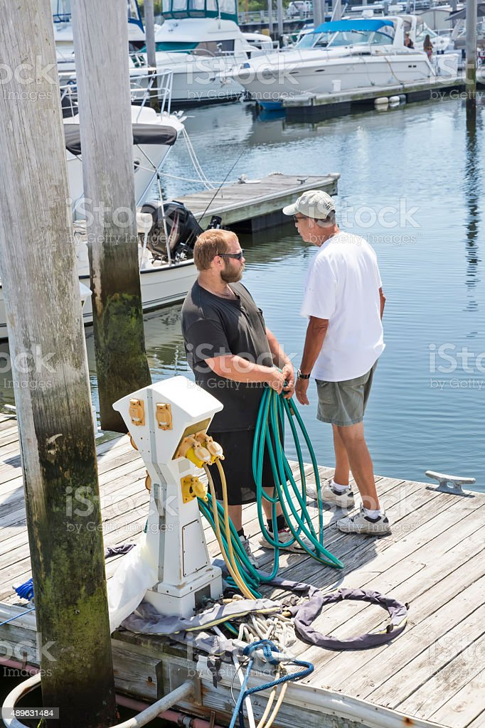 Caucasian man attaching boat's water hoses to source on dock stock photo