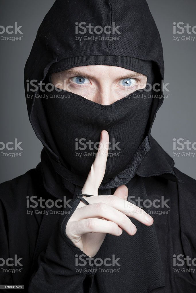 caucasian man disguised as a ninja isolated on grey royalty-free stock photo