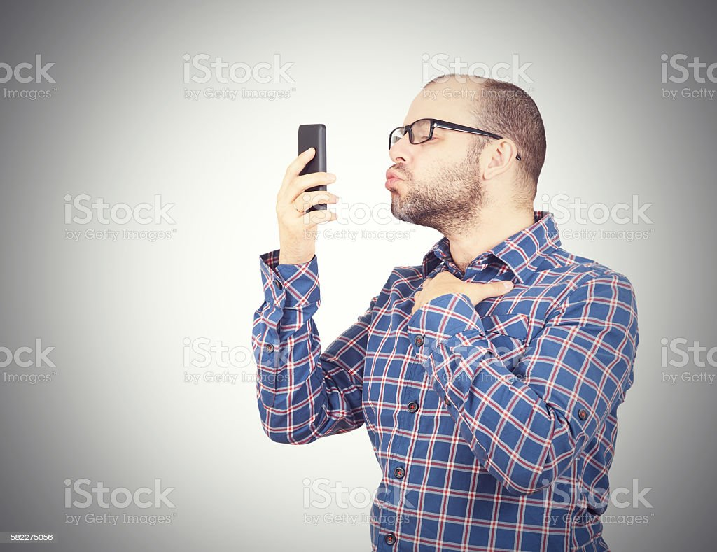 Caucasian man doing a selfie with a kiss. stock photo