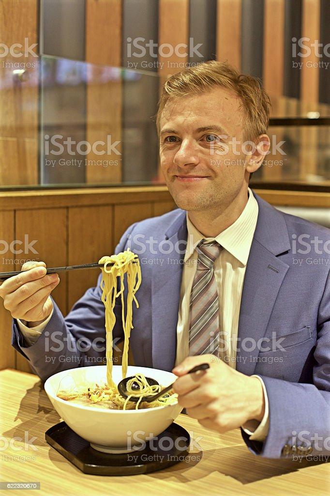 Caucasian man eating noodles in restaurant stock photo