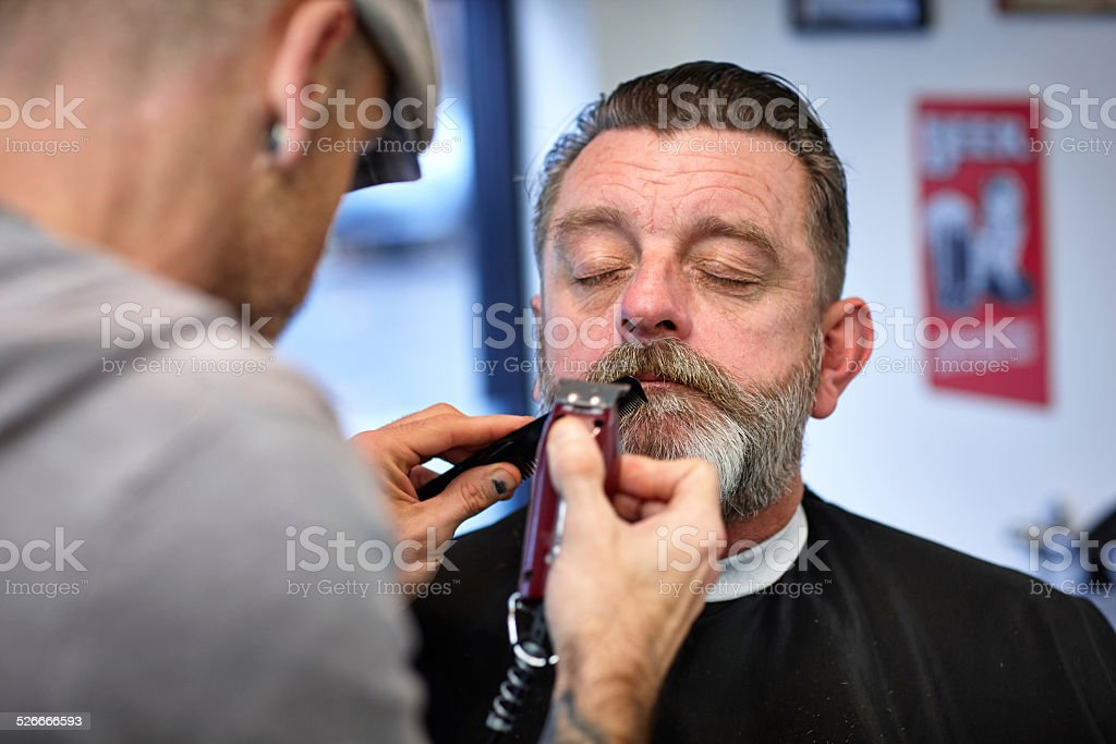 Caucasian man getting his mustache trimmed stock photo
