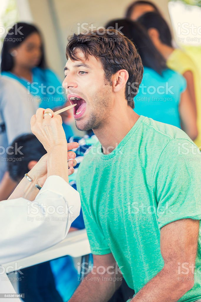 Caucasian man having his mouth and throat examined stock photo
