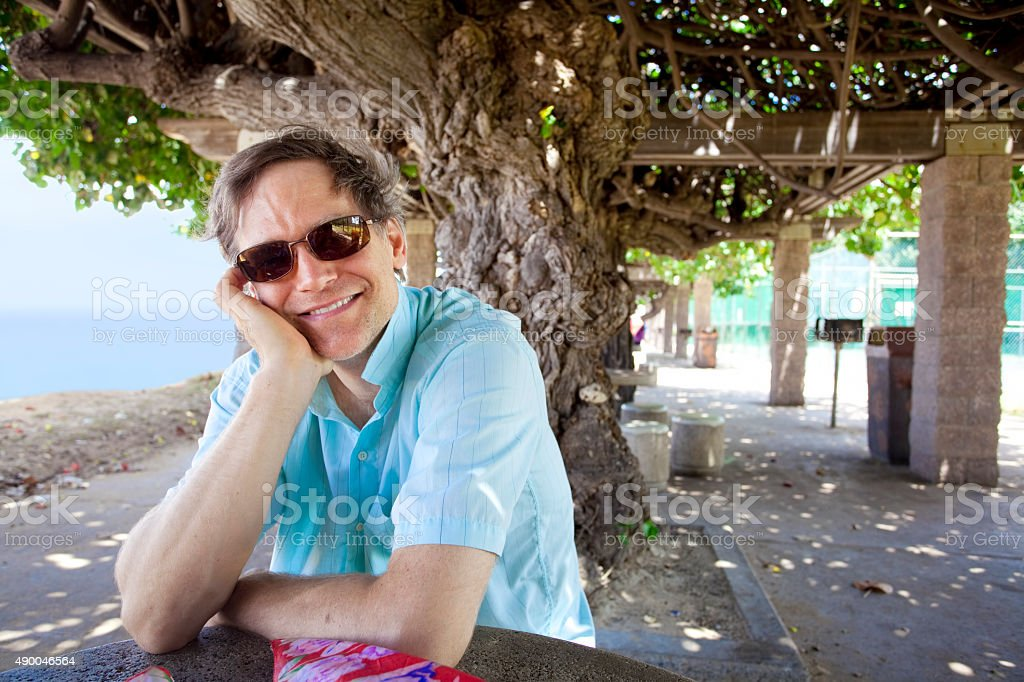 Caucasian man in forties relaxing under shaded tree canopy stock photo