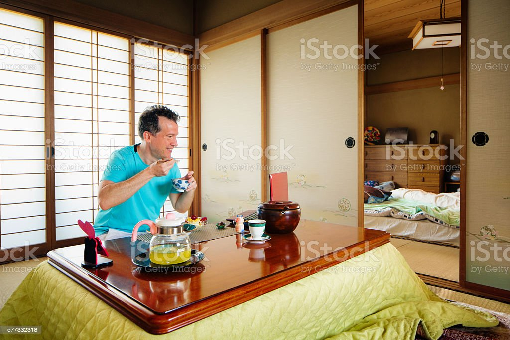 Caucasian man in his Japanese room having breakfast stock photo