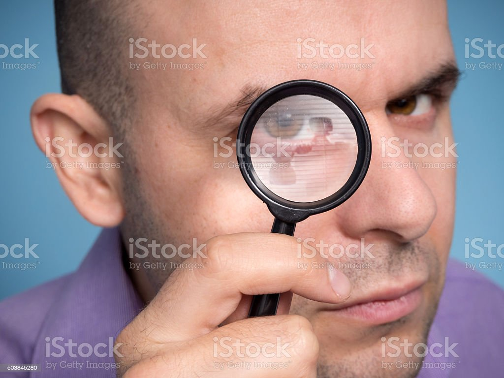 Caucasian man looking magnifying glass stock photo