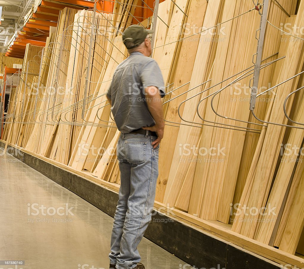 Caucasian man looking, shopping for lumber in a Hardware store royalty-free stock photo
