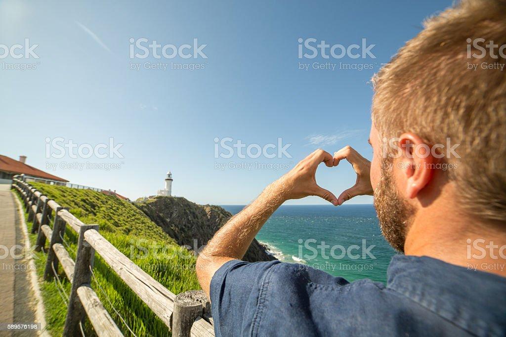 Caucasian man makes heart shape finger frame on seascape stock photo