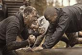 Caucasian man personal trainer coaching mud run team of men