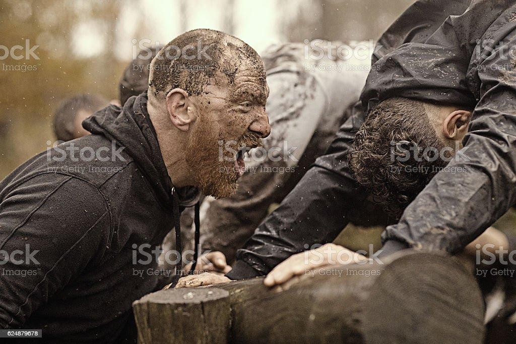 Caucasian man personal trainer coaching mud run team of men stock photo