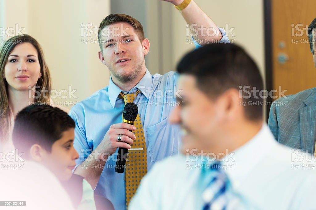 Caucasian man raises hand during town hall meeting stock photo