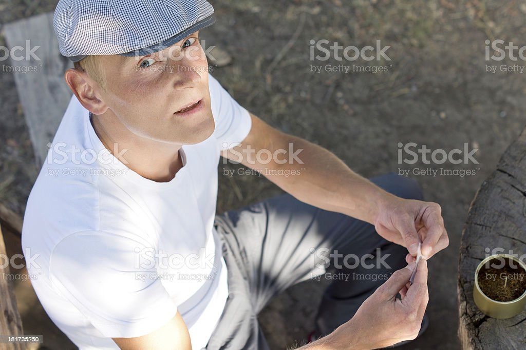 Caucasian man rolling a cigarette in the park royalty-free stock photo