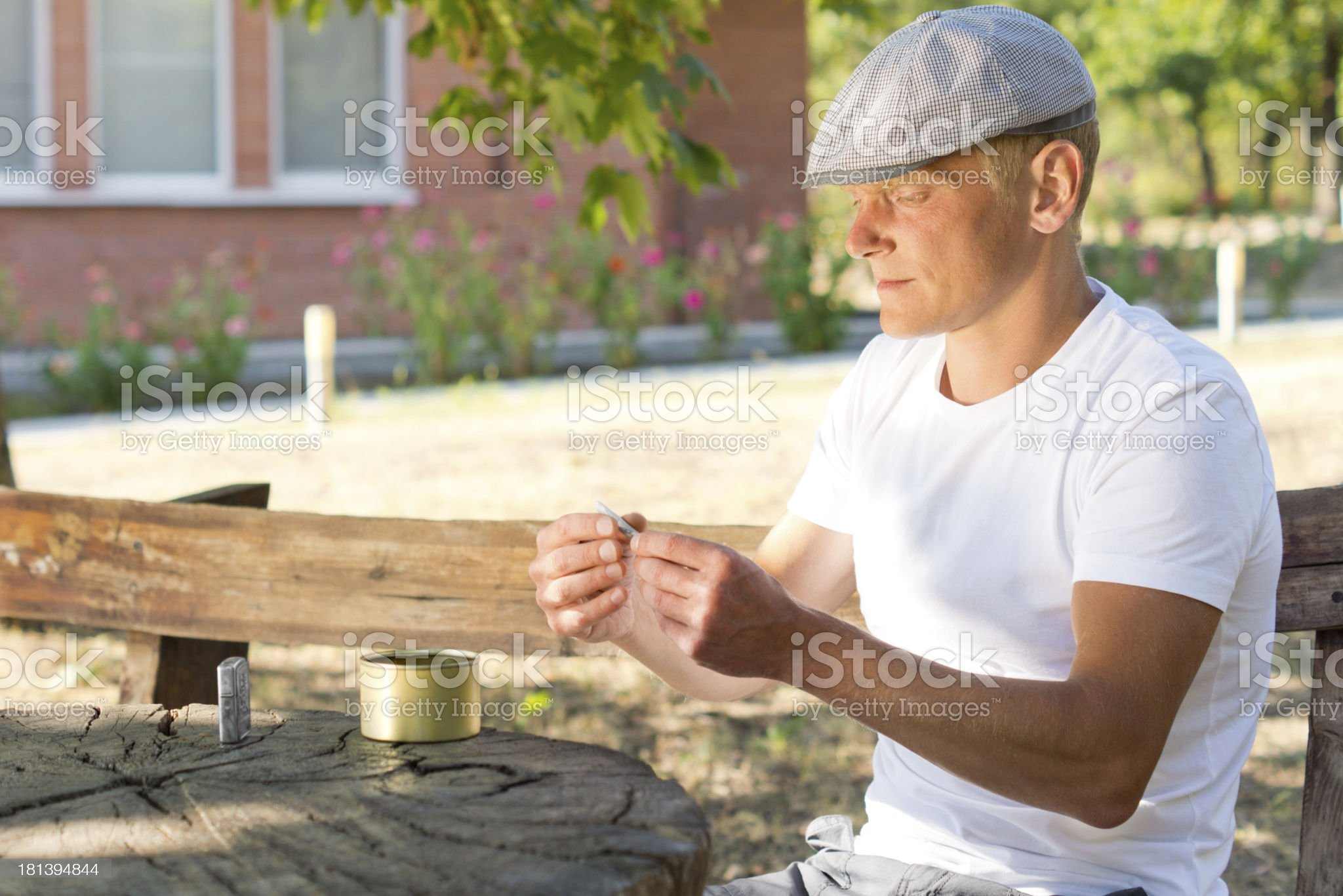 Caucasian man rolling cigarette in a summer day royalty-free stock photo