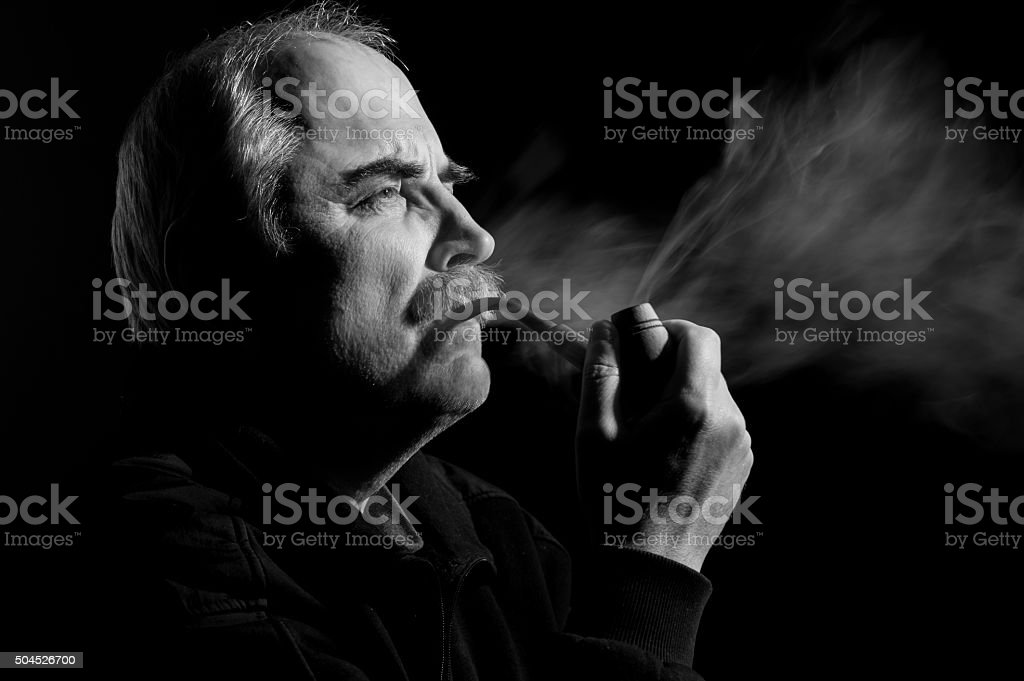 Caucasian man smoking tobacco pipe stock photo
