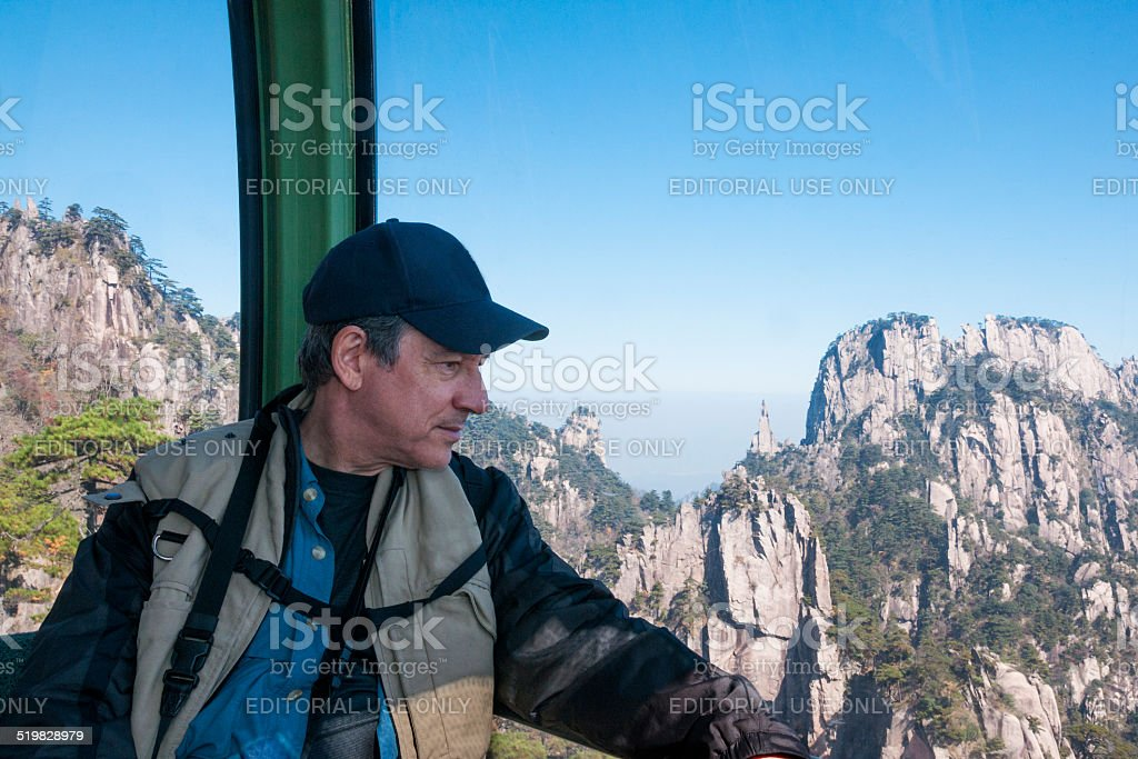 Caucasian man travels on cable car up Yellow Mountain, China stock photo