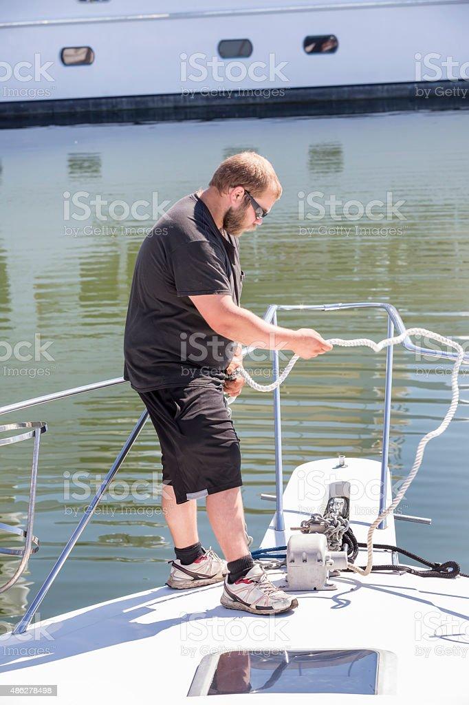 Caucasian man tying up sailboat to dock at a mairina stock photo