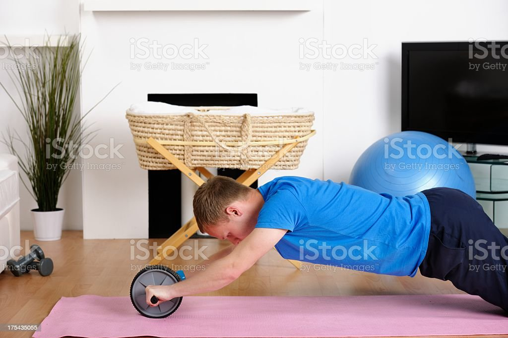 Caucasian Man Using Exercise Wheel At Home stock photo