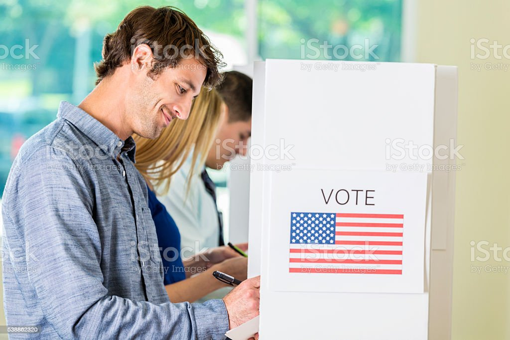 Caucasian Man voting at booth stock photo