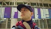 Caucasian man wearing cap looks around near airport terminal departure