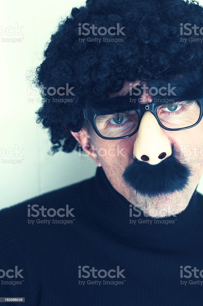 Caucasian Man Wears Disguise with Afro Wig Glasses and Mustache stock photo