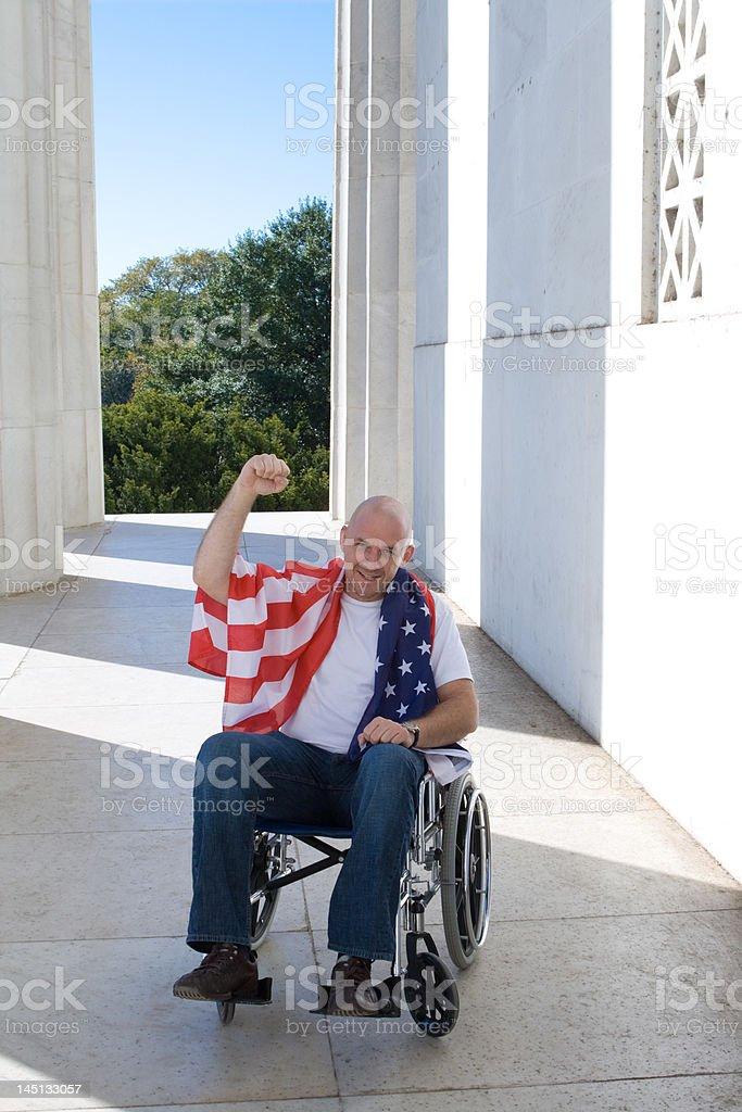 Caucasian Man Wheelchair, American Flag, Raised Fist, Blue Sky royalty-free stock photo