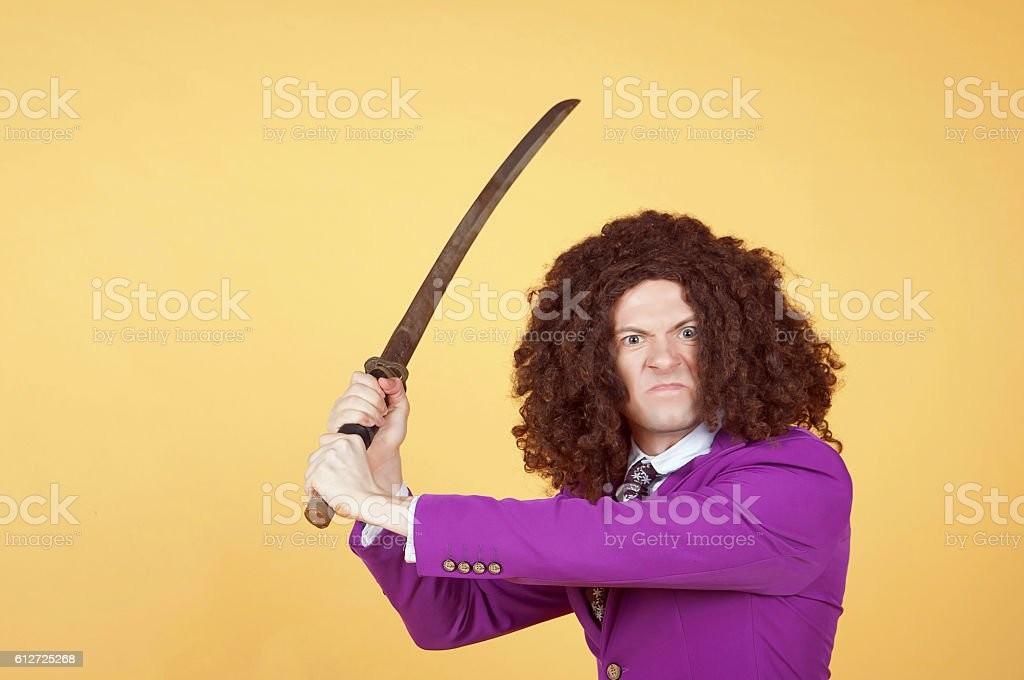 Caucasian man with afro wearing Purple Suit carrying sword stock photo