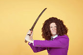 Caucasian man with afro wearing Purple Suit carrying sword
