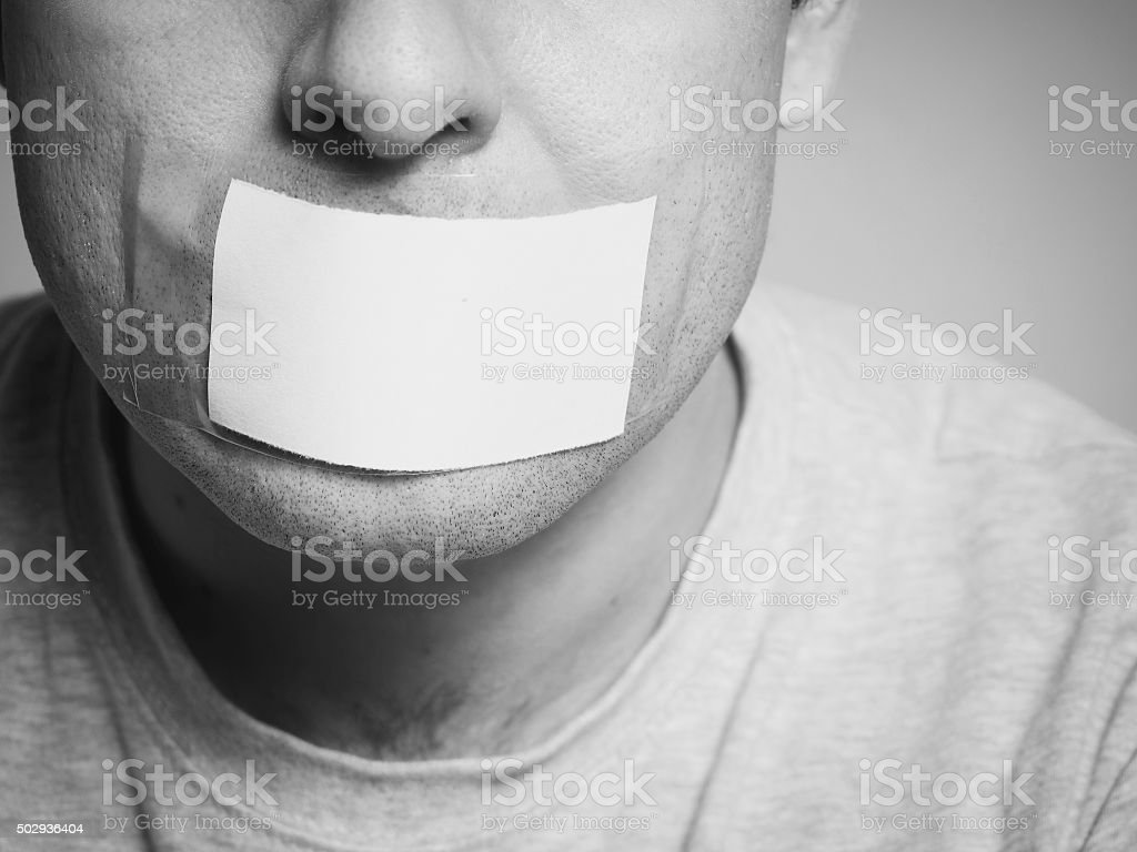 Caucasian man with duct tape on mouth, white . stock photo