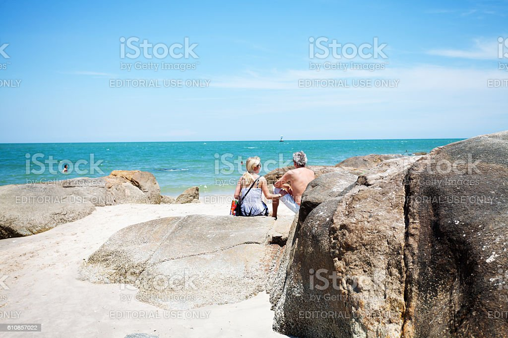 Caucasian mature couple sitting on rocks and beach stock photo