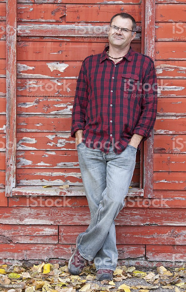 Caucasian Middle Aged Man Leaning Against Red Wood Wall stock photo