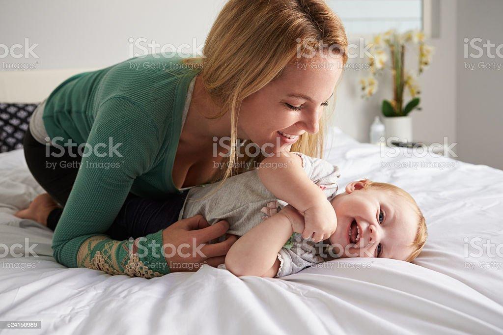 Caucasian mother kneeling on bed, tickling her baby daughter stock photo