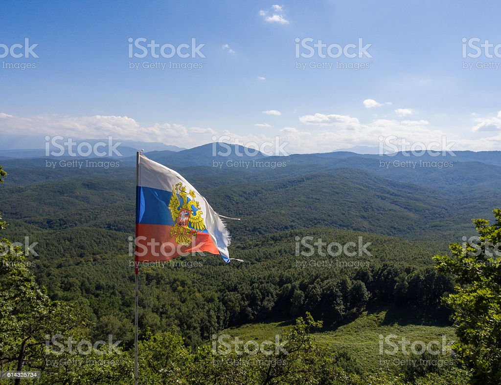 Caucasian mountain landscape on the background of Russian flag stock photo