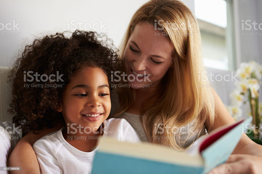 Caucasian mum and smiling black daughter read in bed, close-up stock photo